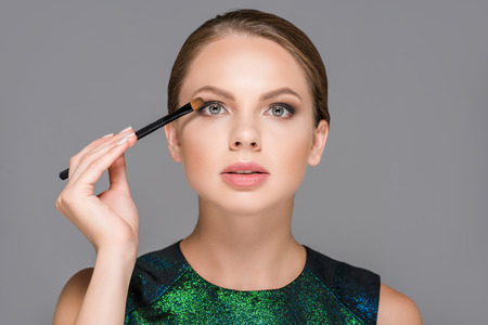 portrait of elegant woman with makeup brush for eyeshadows isolated on grey Stock fotó