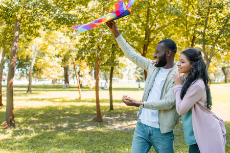side view of happy african american boyfriend holding rainbow kite in park