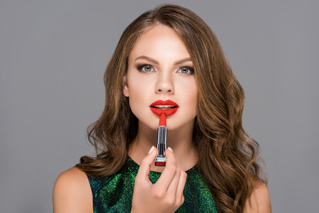 portrait of attractive young woman applying red lipstick isolated on grey