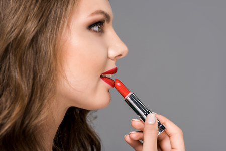 side view of attractive young woman applying red lipstick isolated on grey Stock fotó