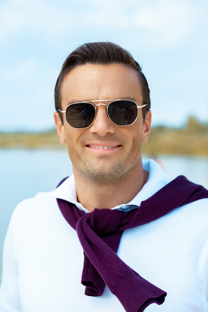portrait of smiling man in sunglasses looking at camera with river on background