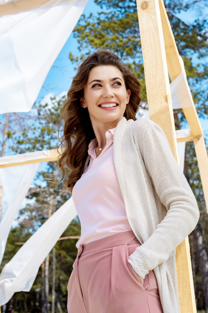 low angle view of happy woman standing near wooden decoration with white curtain lace