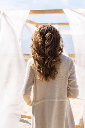 back view of woman standing near wooden decoration with white curtain lace on sandy beach