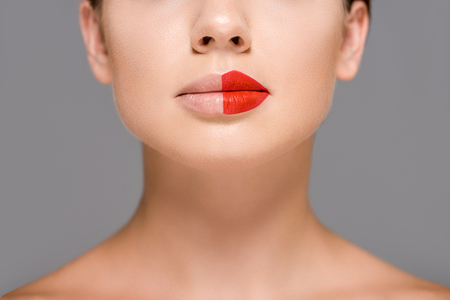 cropped shot of woman with red lipstick on half of mouth isolated on grey Stock fotó - 107678629