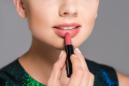 partial view of woman applying lipstick isolated on grey
