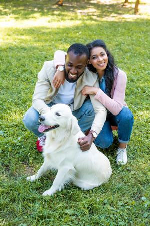 smiling african american couple hugging and squatting near dog in park Reklamní fotografie