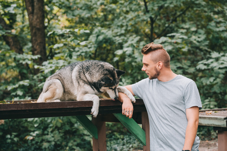 young man with siberian husky dog in park