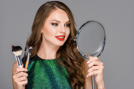 portrait of smiling woman with makeup brushes looking at mirror isolated on grey
