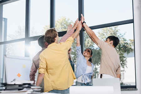 happy businesspeople celebrating success and giving high five in office