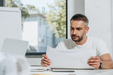 handsome businessman in shirt reading documents in office Stock Photo