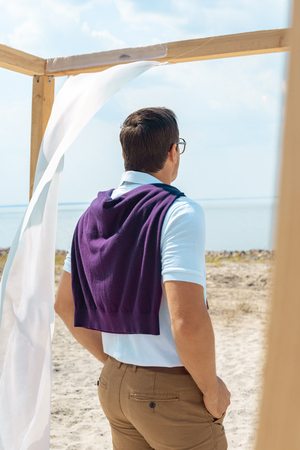 back view of man standing near decoration with white curtain lace on sandy beach Stockfoto
