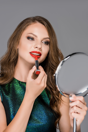 portrait of attractive young woman looking at mirror while applying red lipstick isolated on grey