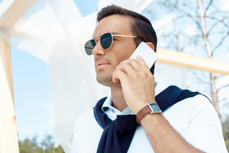 portrait of handsome man in sunglasses talking on smartphone with blue cloudy sky on background