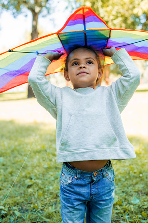adorable african american kid holding rainbow kite above head in park Stock Photo