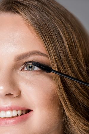 partial view of smiling woman and mascara brush Stock fotó