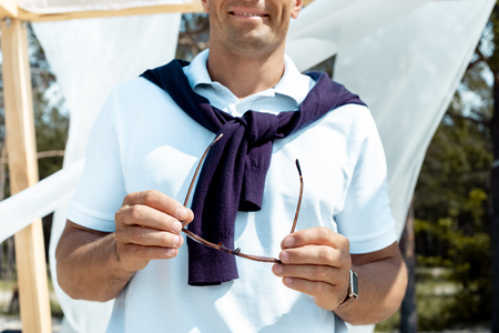 cropped shot of man holding eyeglasses in hands with white curtain lace on background Stockfoto
