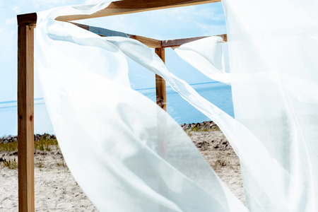 close up view of wooden decoration with white curtain lace, blue cloudy sky and river on background Stockfoto
