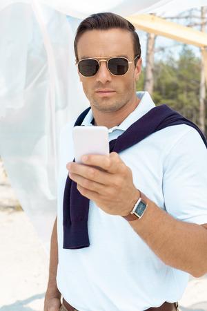portrait of handsome man in sunglasses using smartphone