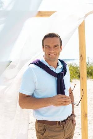 portrait of stylish smiling man with eyeglasses standing at decoration with white curtain lace on sandy beach