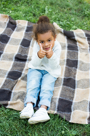 adorable african american kid sitting on blanket and showing thumbs up in park Imagens
