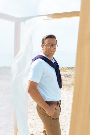handsome man in eyeglasses standing near decoration with white curtain lace on sandy beach Stockfoto