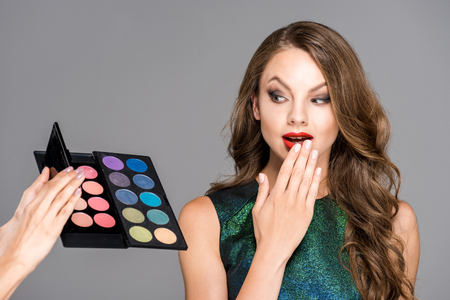 partial view of makeup artist showing eyeshadows palette to shocked model isolated on grey Reklamní fotografie