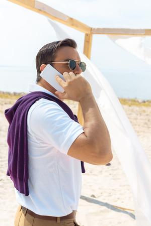 side view of stylish man in sunglasses talking on smartphone on sandy beach Stockfoto