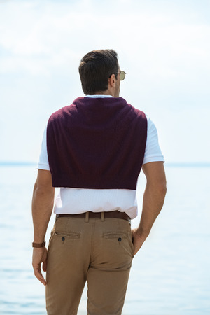 rear view of man standing and looking at river on summer day