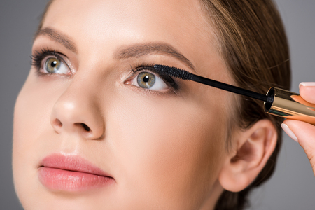 portrait of attractive woman applying black mascara while looking away
