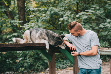 handsome man with siberian husky dog in park