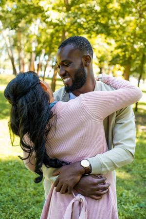happy african american couple cuddling in park Stock fotó
