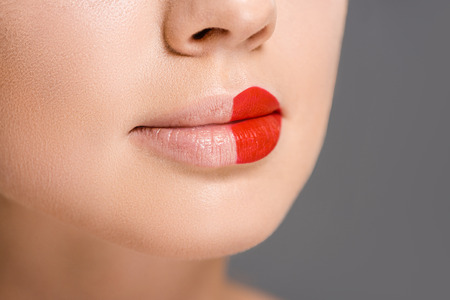 cropped shot of woman with red lipstick on half of mouth isolated on grey Stock fotó