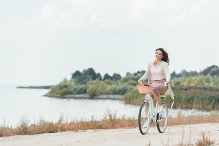 smiling woman riding retro bicycle on sandy riverside Banco de Imagens
