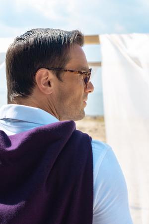 back view of pensive man in eyeglasses on sandy beach Stockfoto