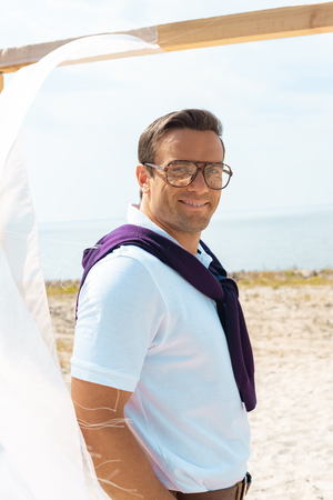 smiling man in eyeglasses standing near decoration with white curtain lace on sandy beach