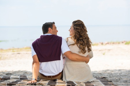 back view of romantic couple resting on blanket on sandy beach