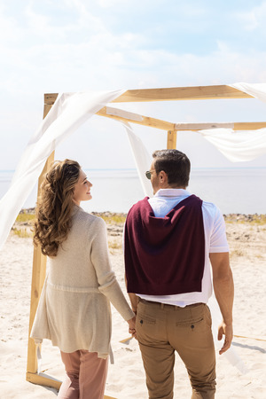rear view of happy couple on sandy beach with white curtain lace decoration Stockfoto