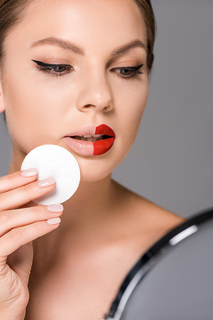 portrait of young woman with red lipstick on half of lips and sponge looking at mirror isolated on grey