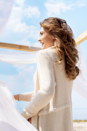 side view of happy woman looking away with white curtain lace on background