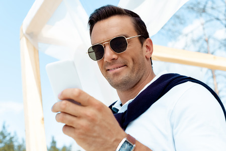 portrait of handsome man in sunglasses using smartphone with blue cloudy sky on background