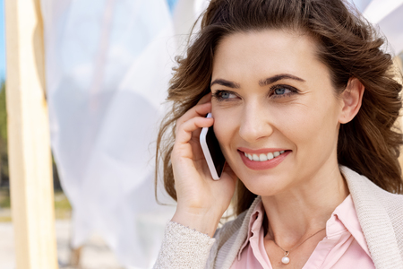 portrait of smiling woman talking on smartphone with white curtain lace on background Stockfoto