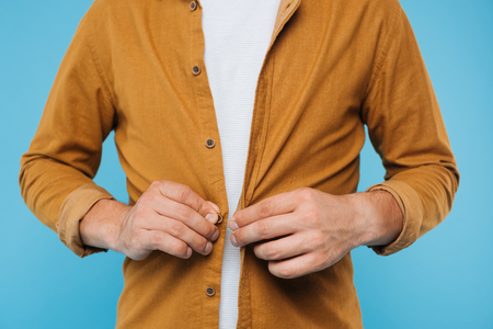 cropped image of man buttoning brown shirt isolated on blue