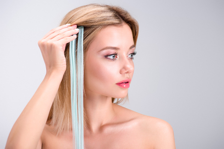 attractive young woman applying grey clip-on hair strand isolated on grey