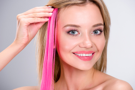 happy young woman applying pink clip-on hair strand isolated on grey