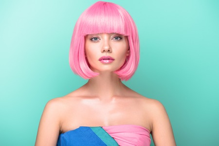 young woman with pink bob cut looking at camera isolated on turquoise