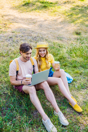 young couple with coffee to go using laptop in park Banco de Imagens