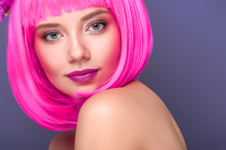 close-up portrait of beautiful young woman with pink bob cut looking at camera isolated on violet