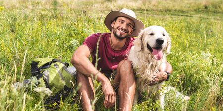 traveler sitting with golden retriever dog on green meadow Banco de Imagens