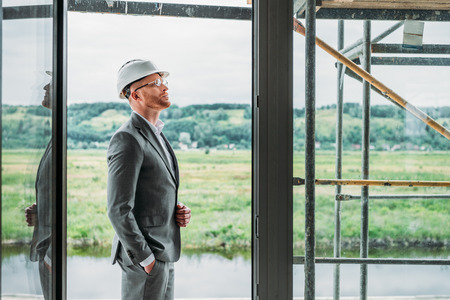 side view of handsome architect in suit and hard hat standing on terrace at construction site Imagens