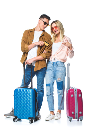 young travelling couple with suitcases and credit card isolated on white Banco de Imagens